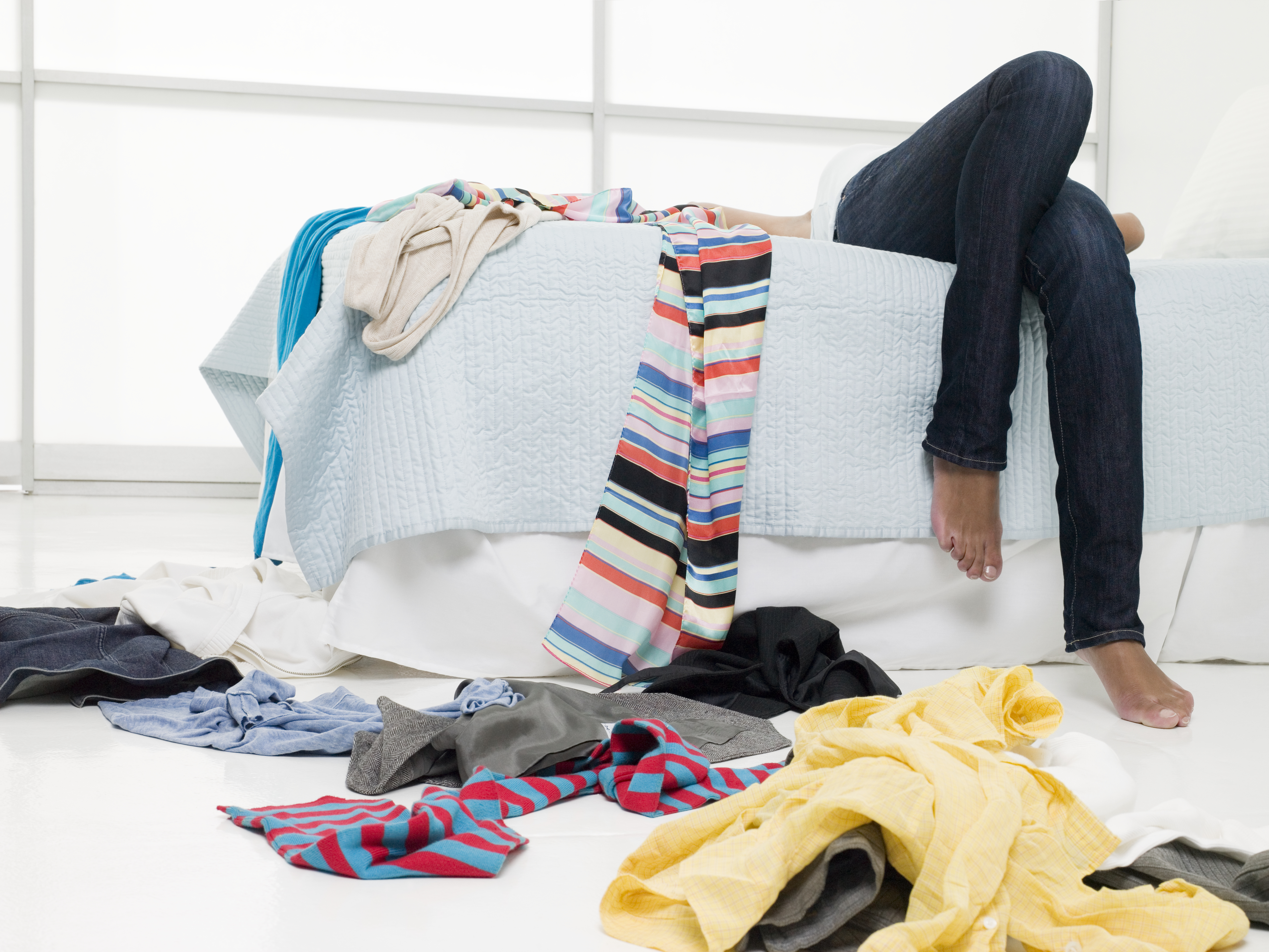 A person lays back on their bed with a mess of clothes around them and on the floor.