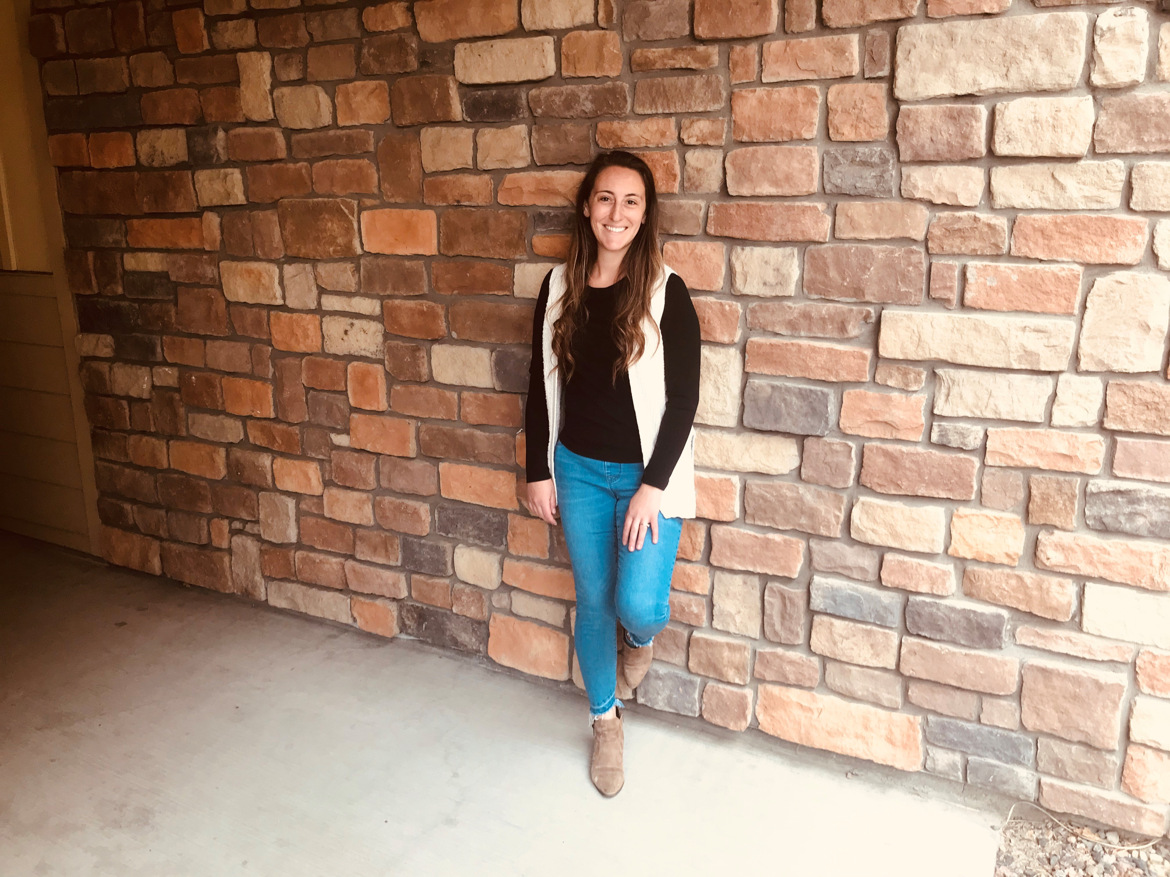 Miranda Guyaux-Mitchell smiles and poses standing in front of a brick wall.
