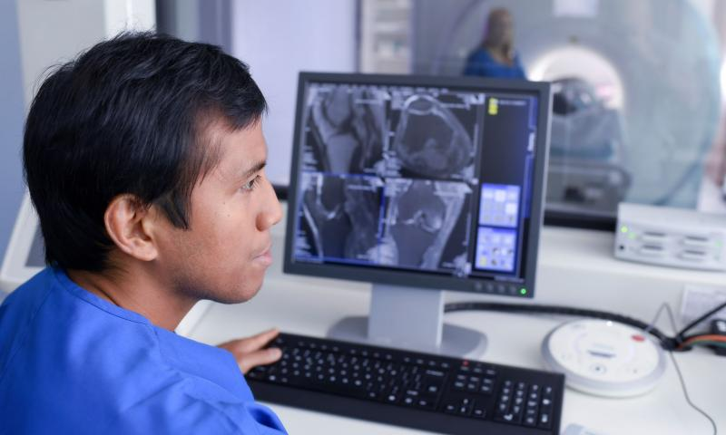 Healthcare technician viewing a diagnostic scan on a computer screen
