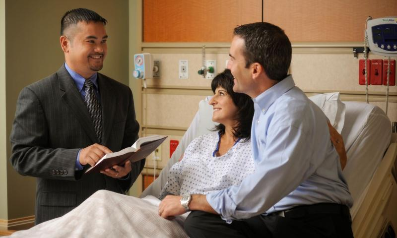 Chaplain visiting with patient and family in hospital room