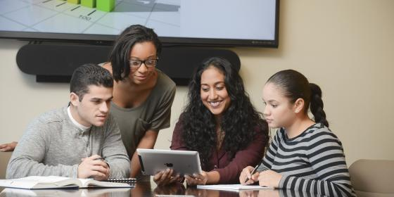 An MHA professor and three students review course material on an iPad.