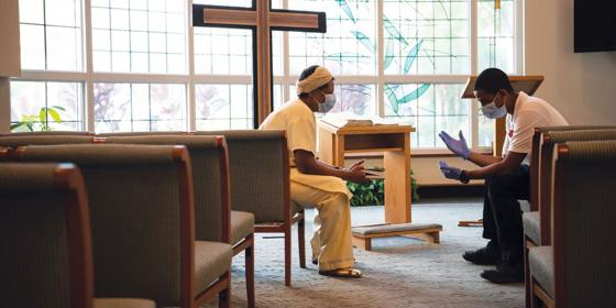 A hospital staff member conversing with a visitor in a chapel.
